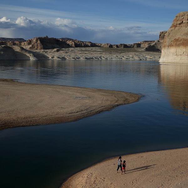People walk on a beach the used to be the bottom of Lake Powell, in the Colorado River Basin, near Big Water, Utah, on March 29, 2015. (Credit: Justin Sullivan / Getty Images)