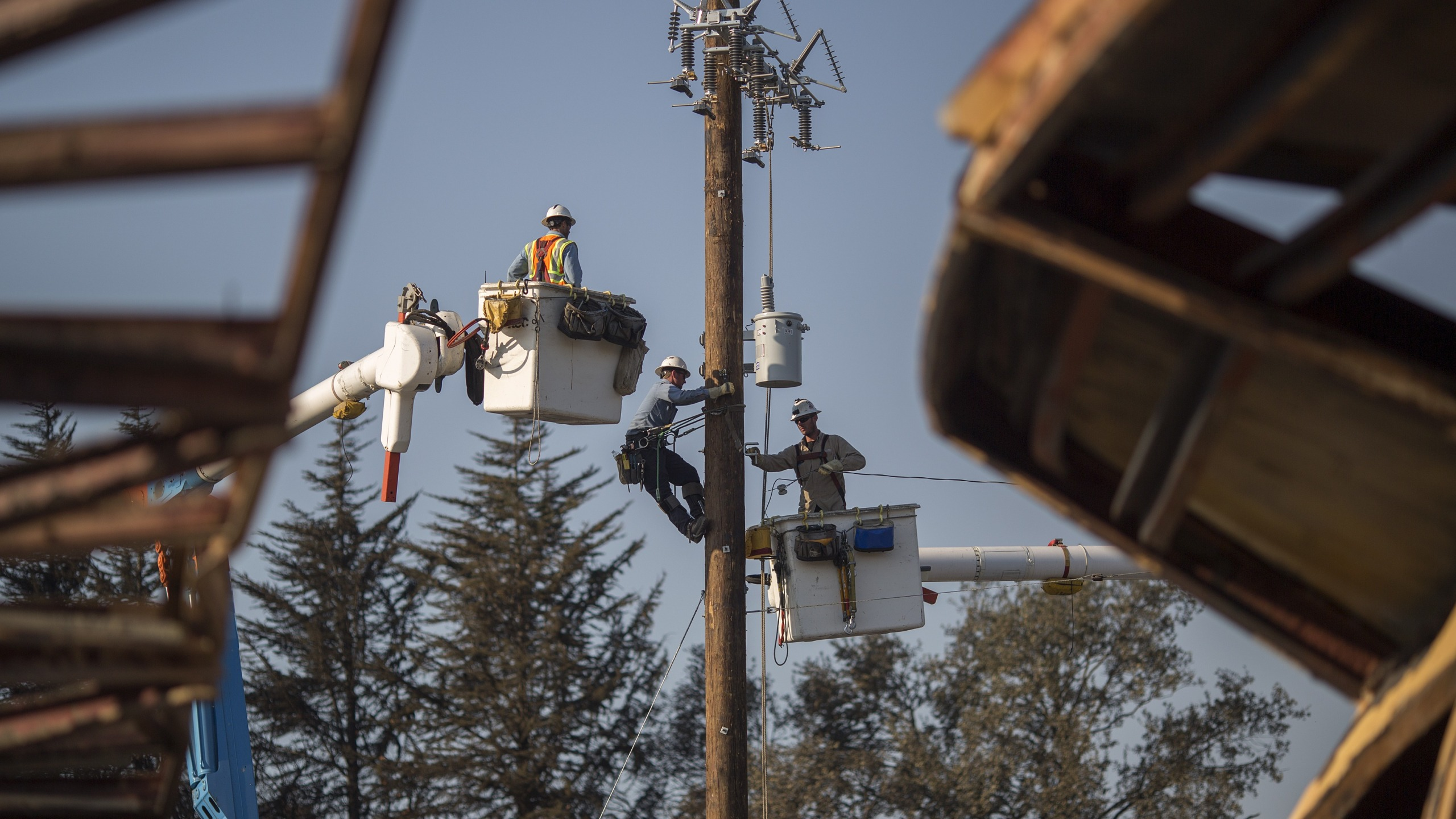 Pacific Gas and Electric Company crews work to restore power near fire-damaged Cardinal Newman High School on Oct. 14, 2017 in Santa Rosa. (Credit: David McNew/Getty Images)
