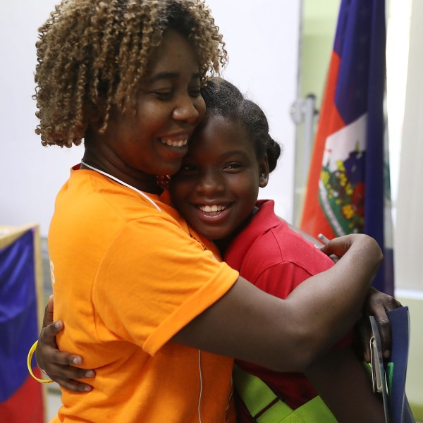 Santcha Etienne, left, hugs Ronyde Christina Ponthieux, 10, after she spoke about her father, originally from Haiti, who is here under Temporary Protective Status during a press conference on Nov. 6, 2017, in Miami, Florida. (Credit: Joe Raedle / Getty Images)