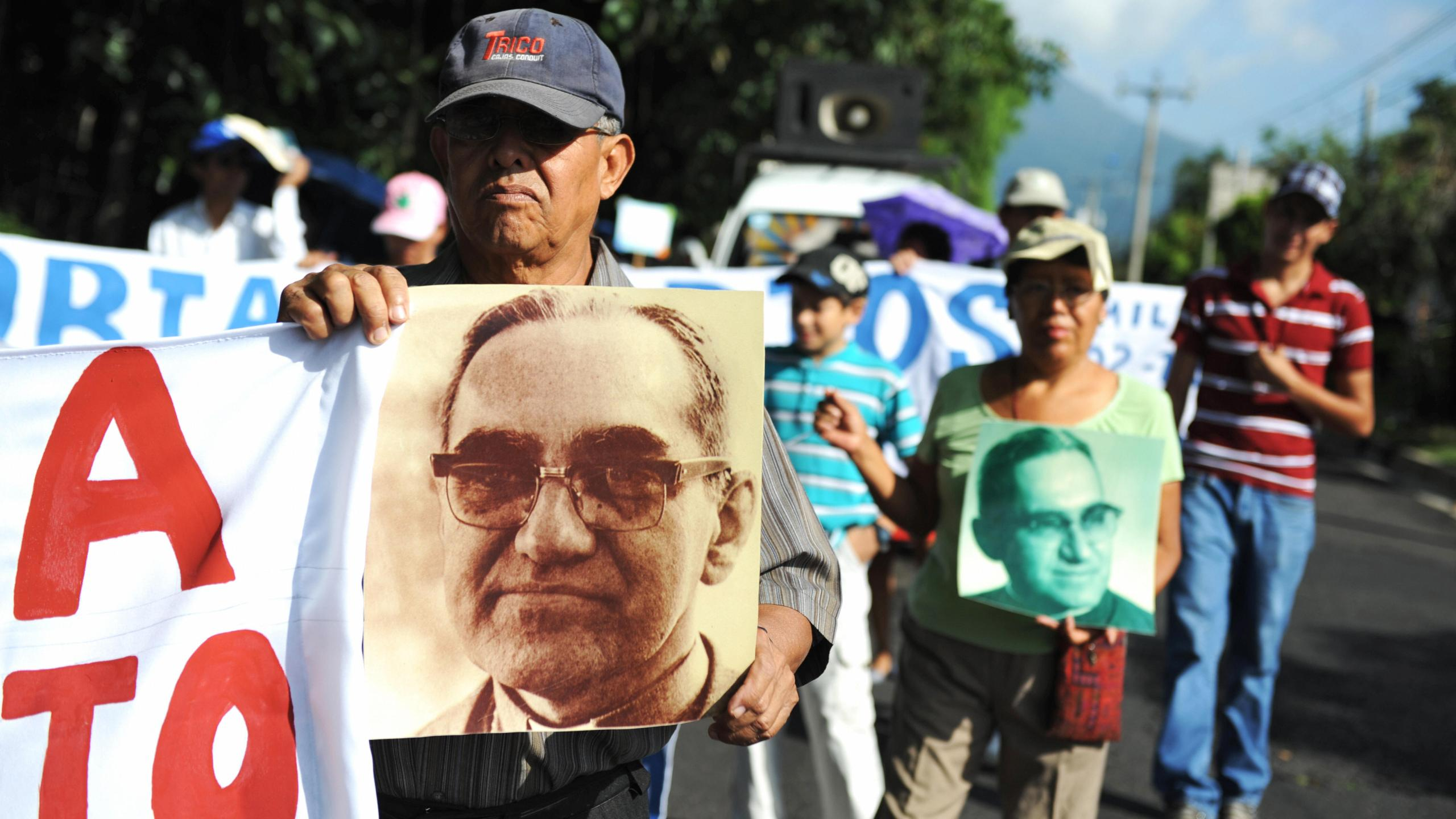Catholic faithfuls participate in a march to celebrate the 92nd birthday of the late archbishop of San Salvador, Oscar Arnulfo Romero, carrying signs and pictures portraying him, in San Salvador on Aug. 15, 2009.(Credit: Jose CABEZAS/AFP/Getty Images)