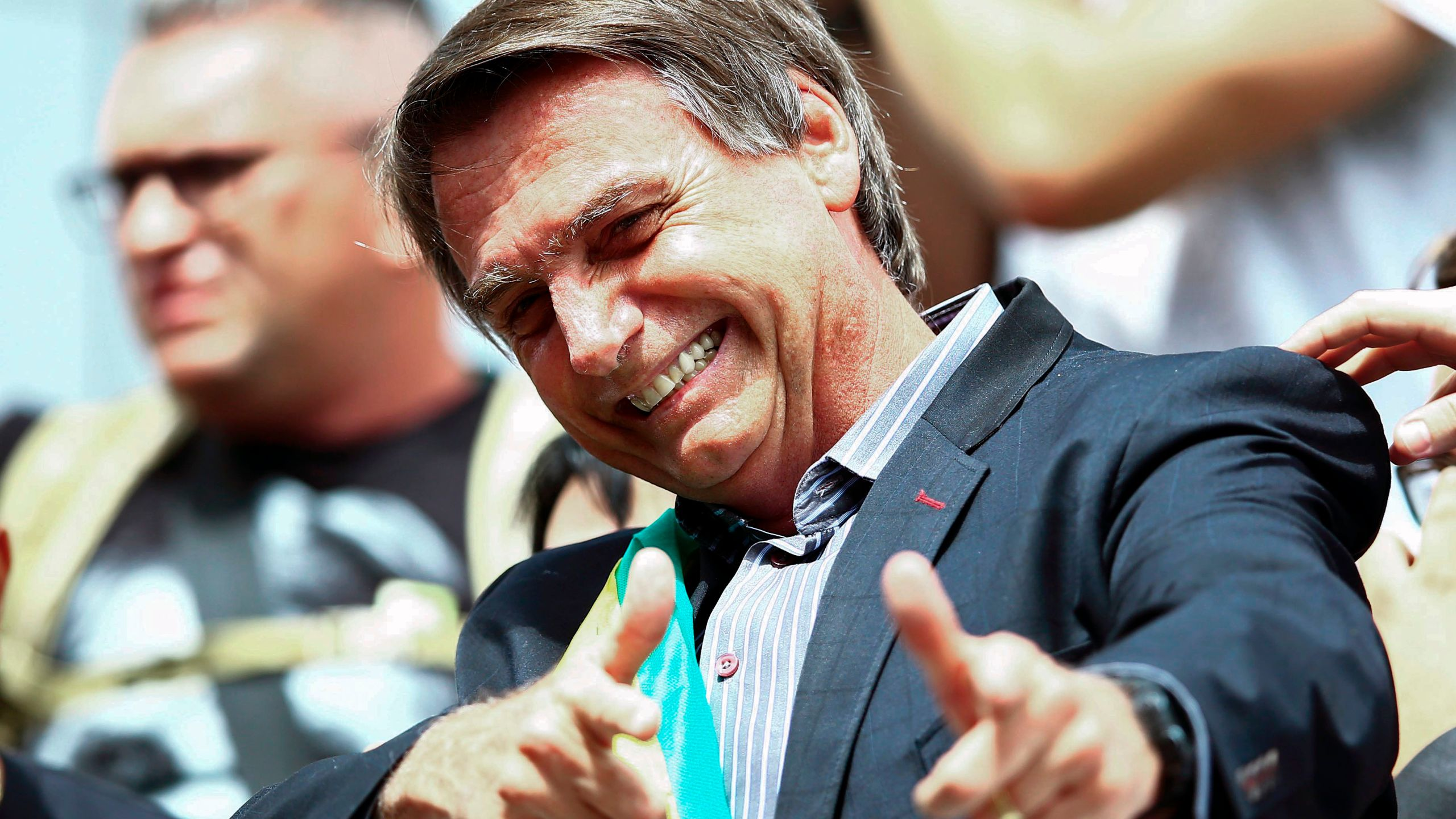 Jair Bolsonaro gives a thumbs up to supporters during a rally at Afonso Pena airport in Curitiba, Brazil on March 28, 2018. (Credit: HEULER ANDREY/AFP/Getty Images)