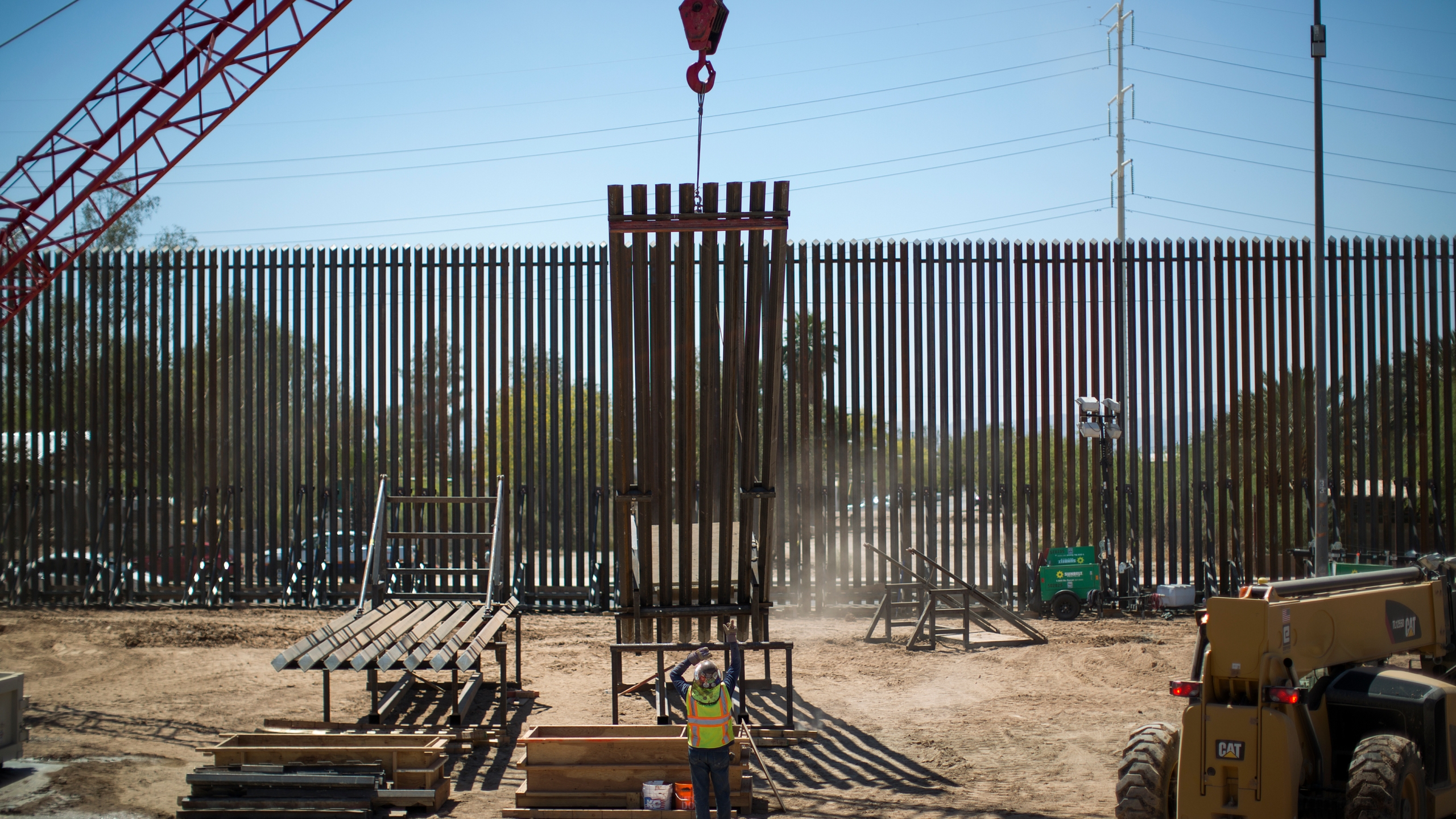 Construction of a new fence takes place as Department of Homeland Security Secretary Kirstjen Nielsen tours a replacement border fence construction site in Calexico on April 18, 2018. (Credit: David McNew / Getty Images)