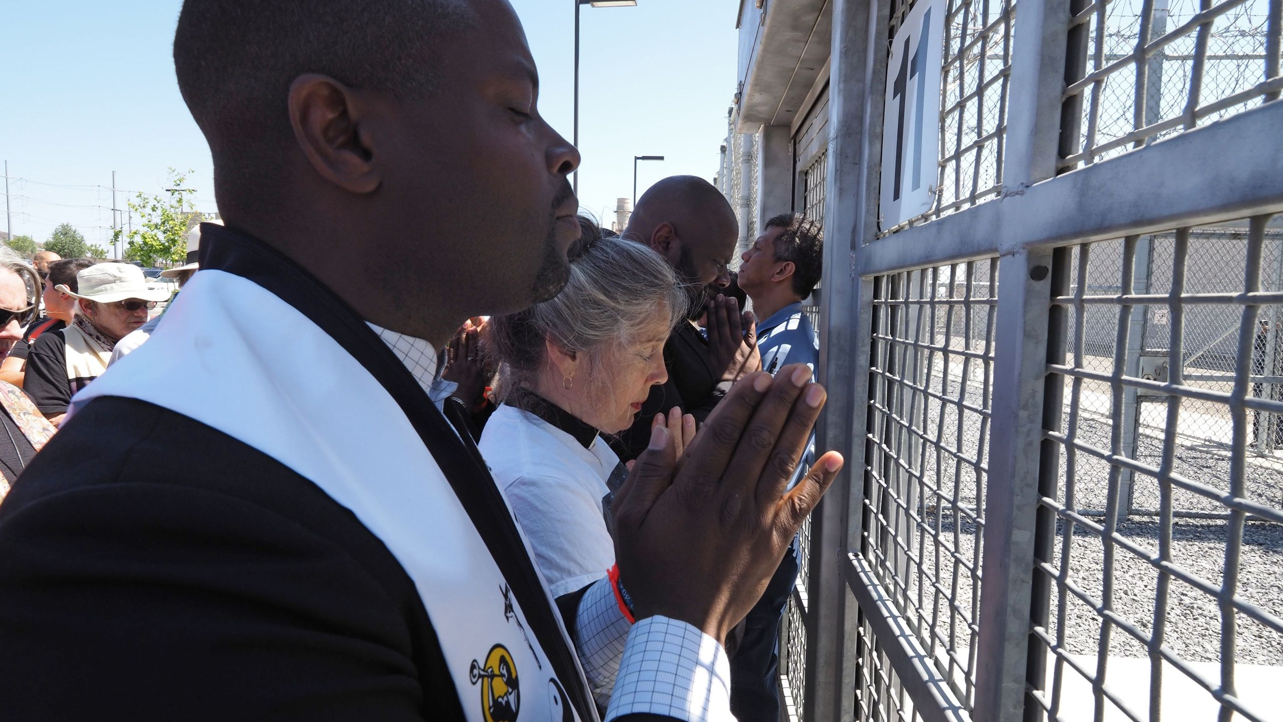 Members of the clergy pray at the entrance to the Otay Mesa Detention Center during a demonstration against U.S. immigration policy that separates children from parents on June 23, 2018. (Credit: Robyn Beck / AFP / Getty Images)