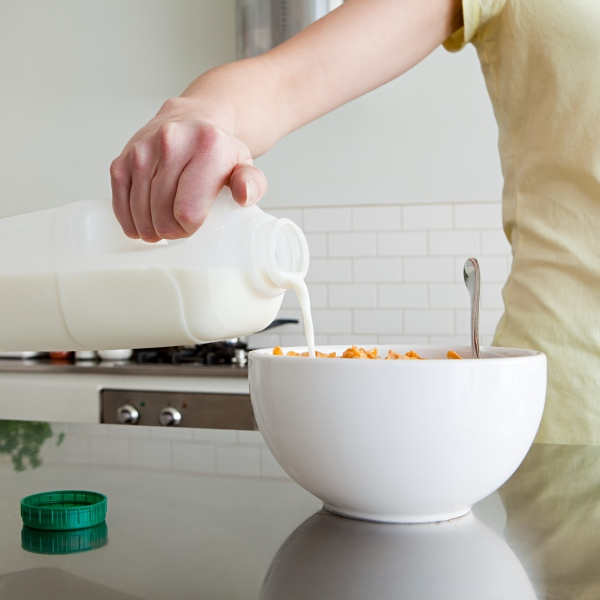 A woman is pouring milk onto cereal in this file photo. (Credit: Getty Images)