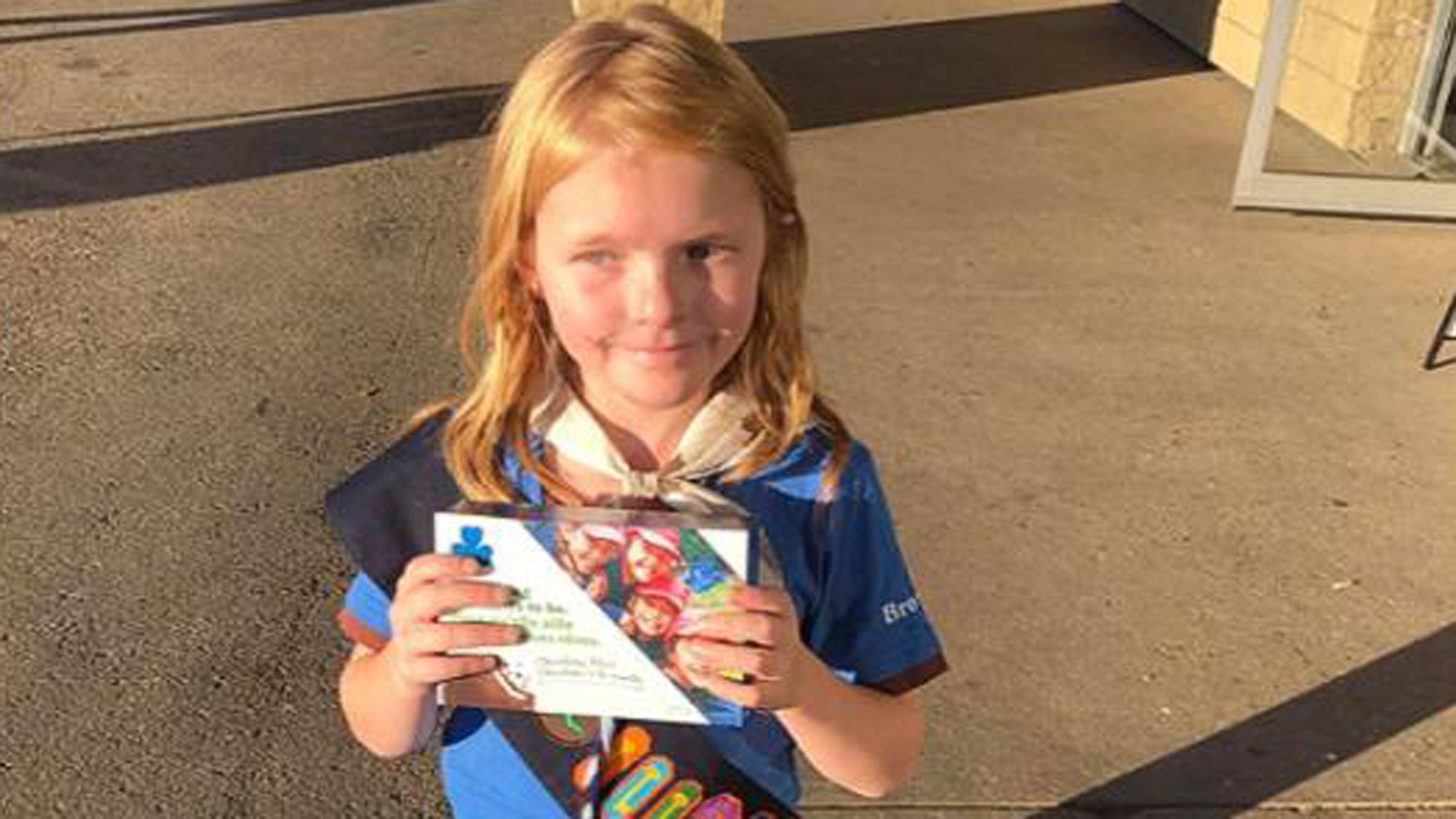 Elina Childs is seen holding a box of Girl Scout cookies.(Credit: Seann Childs via CNN Wire)