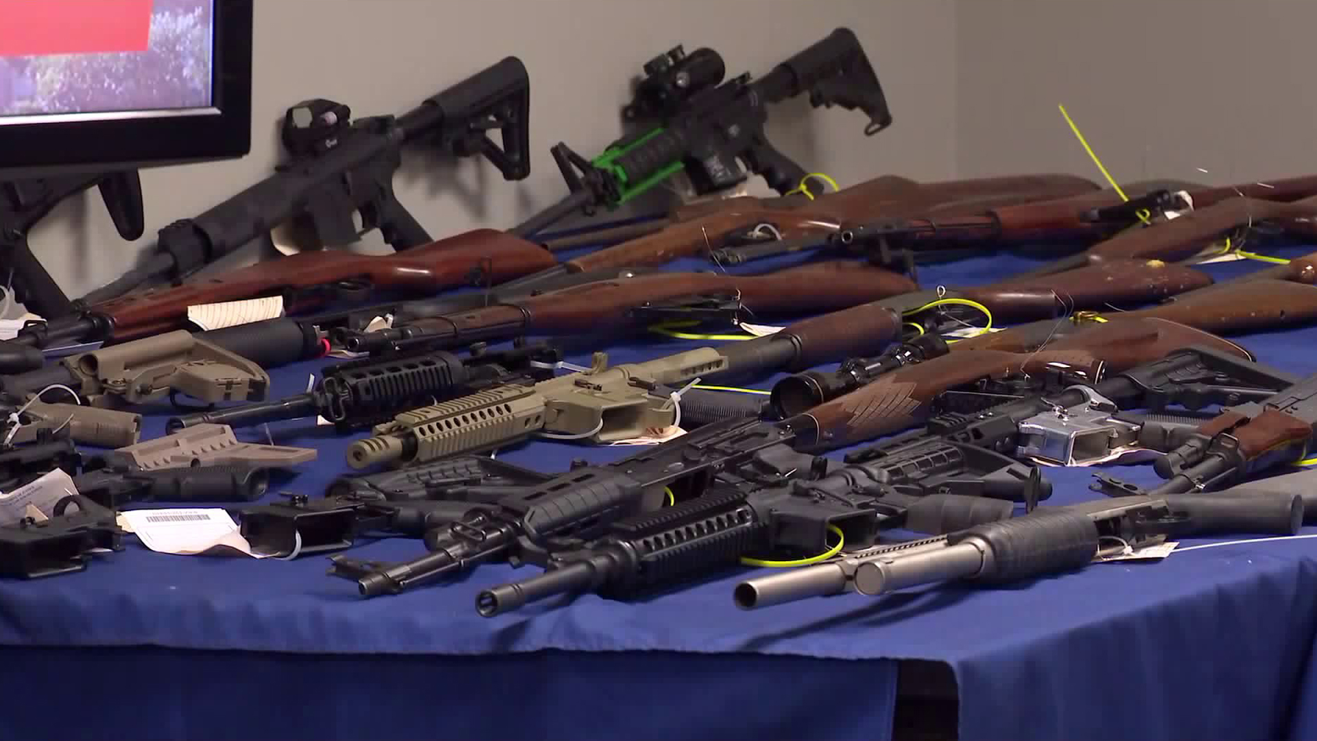 Authorities display 63 seized guns during a press conference to announce a major crackdown targeting gang members in Riverside County on Oct. 19, 2018.