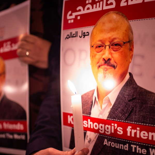 People hold posters picturing Saudi journalist Jamal Khashoggi and lightened candles during a gathering outside the Saudi Arabia consulate in Istanbul, on Oct. 25, 2018. (Credit: YASIN AKGUL/AFP/Getty Images)
