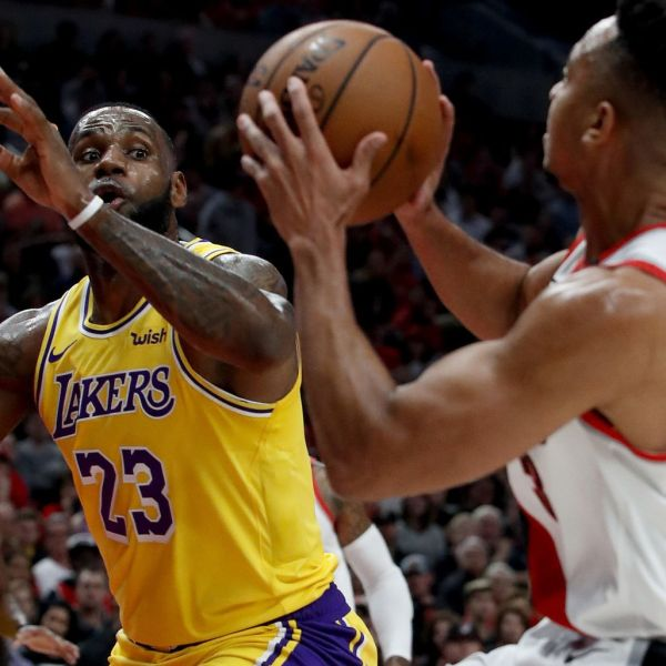 LeBron James prepares to challenge a shot by Trail Blazers guard CJ McCollum in the season opener on Oct. 18, 2018, two days before he makes his Staples Center debut. (Credit: Luis Sinco / Los Angeles Times)