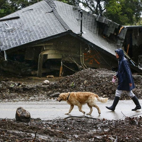 Loreen Zakem walks her dog past one of the homes destroyed in a January debris flow along Montecito Creek in this undated photo. (Credit: Robert Gauthier / Los Angeles Times)