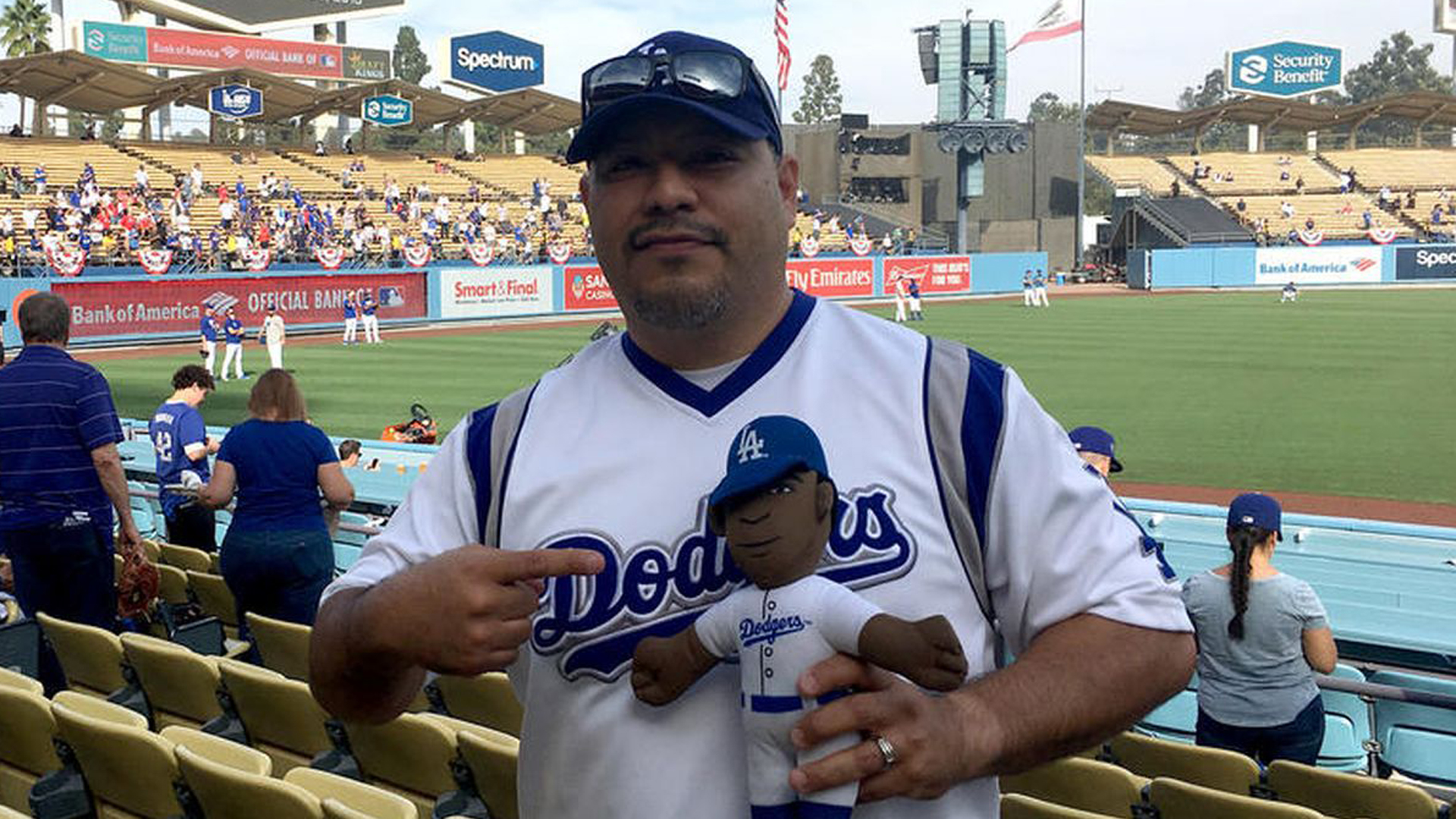 Isaac Tellez lives in Arkansas but he's a die-hard Dodgers fan. Here, he carries a stuffed doll of Yasiel Puig, who he calls 'Lil Puig,' into Game 5 of the 2018 World Series against the Boston Red Sox at Dodger Stadium in L.A. on Oct. 28, 2018. (Credit: Hailey Branson-Potts / Los Angeles Times)