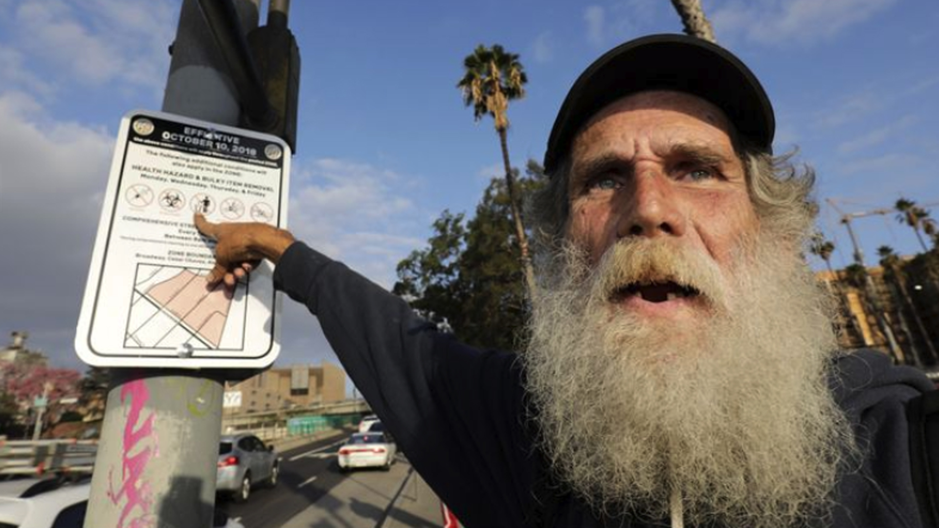 "David Ruther, who has been homeless for the last 12 years, points to a sign declaring a ""special enforcement zone"" posted by the city near a new shelter in El Pueblo historic district in this undated photo. (Credit: Irfan Khan / Los Angeles Times)"