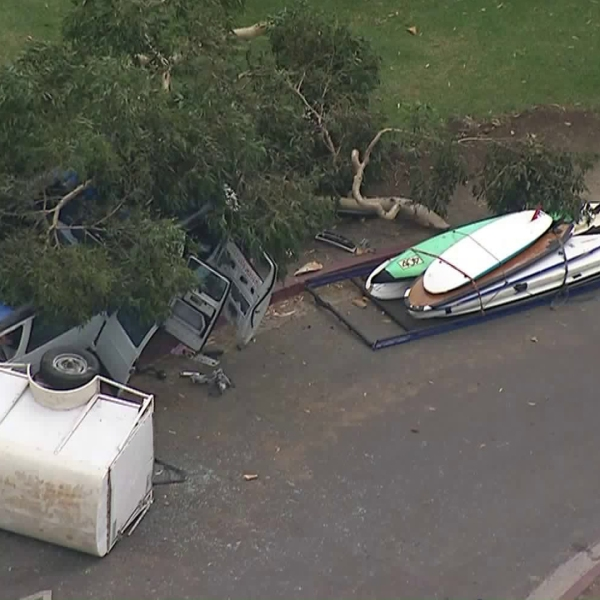 A trailer and a number of surfboards are seen next to a van that appeared to have slammed into a tree in Dana Point on Oct. 3, 2018. (Credit: KTLA)