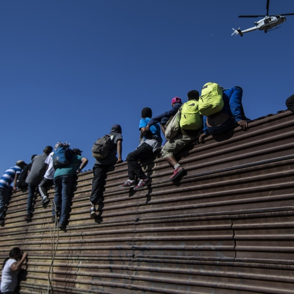 A group of Central American migrants -mostly Hondurans- climb a metal barrier on the Mexico-U.S. border near El Chaparral border crossing, in Tijuana, Baja California State, Mexico, on November 25, 2018. (Credit: PEDRO PARDO/AFP/Getty Images)