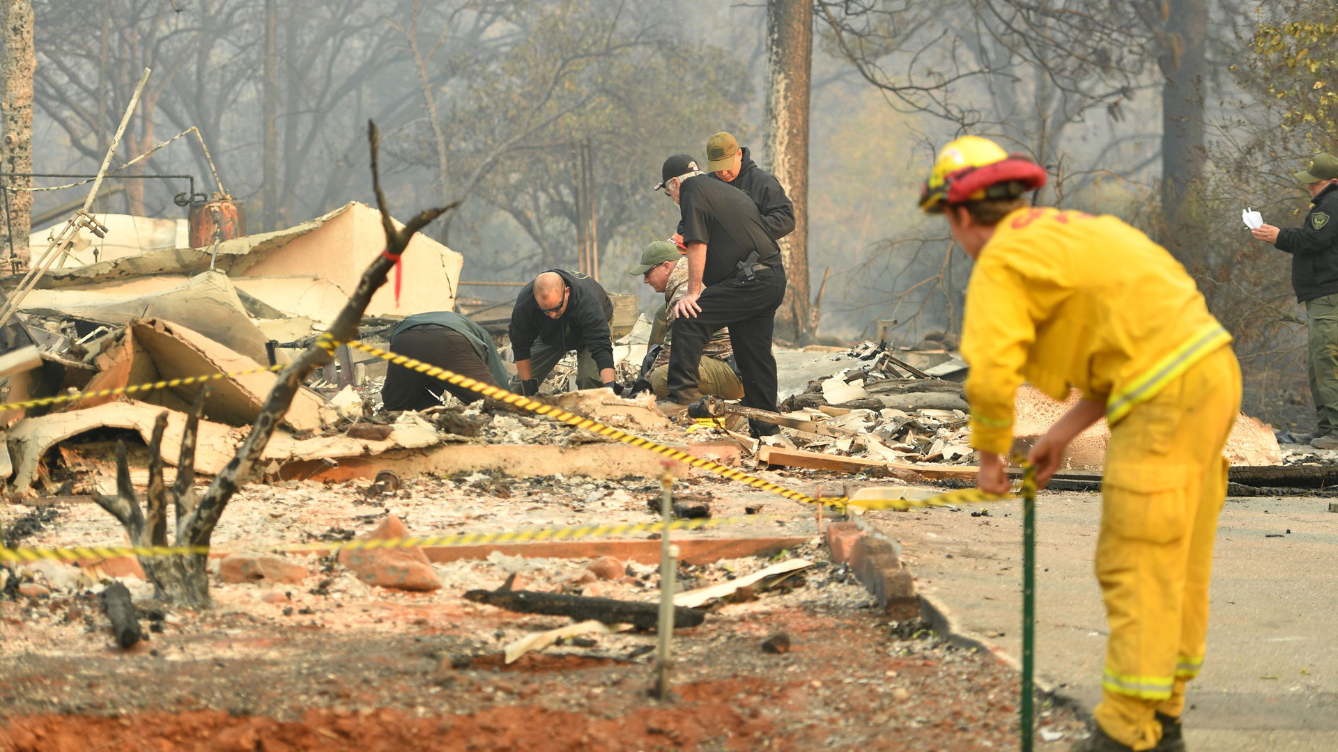 A CalFire firefighter sets up tape as Yuba and Butte County Sheriff officers recover a body at a burned out residence in Paradise on November 10, 2018. (Credit: JOSH EDELSON/AFP/Getty Images)