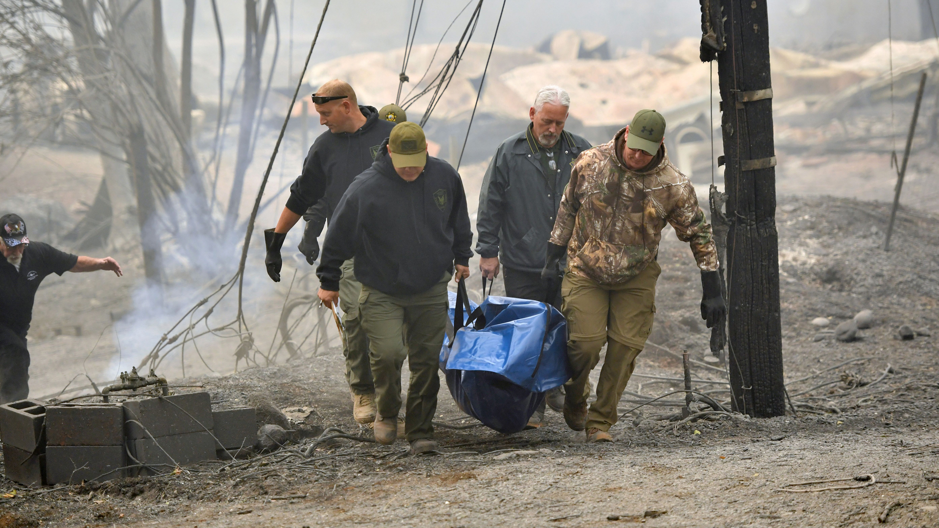 Yuba and Butte County Sheriff officers carry a body away from a burned residence in Paradise on November 10, 2018. (Credit: JOSH EDELSON/AFP/Getty Images)