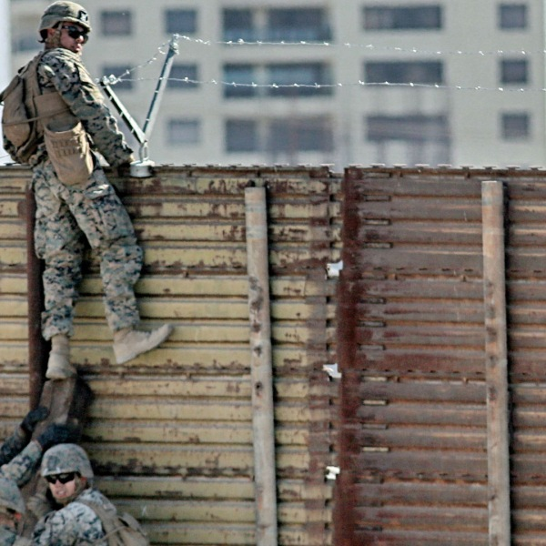 U.S. Marines place barbed wire atop fencing along the U.S.-Mexico border in San Ysidro, California, on Nov. 9, 2018. (Credit: SANDY HUFFAKER/AFP/Getty Images)