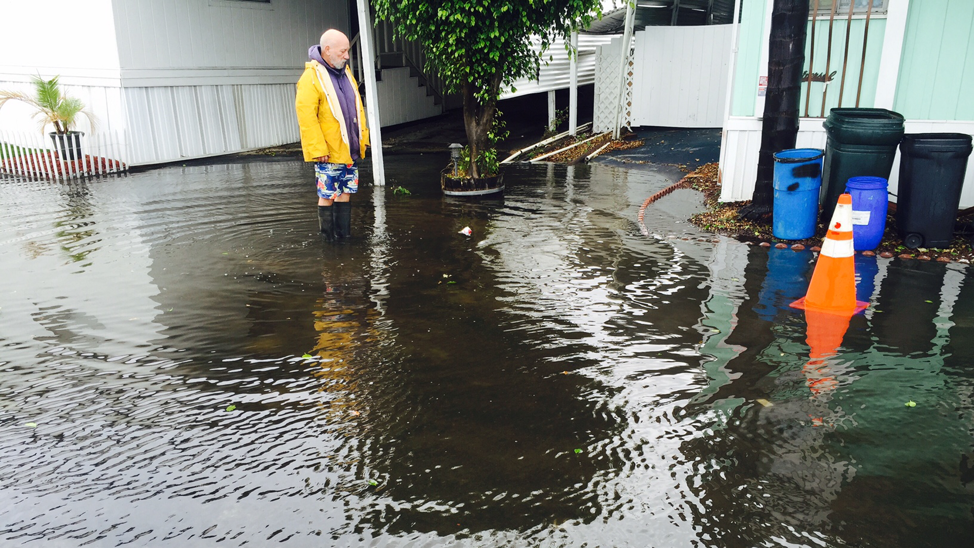 A resident of Friendly Village in Long Beach is seen standing in a flooded roadway outside his mobile home in this undated photo. (Courtesy Gina Fernandes)