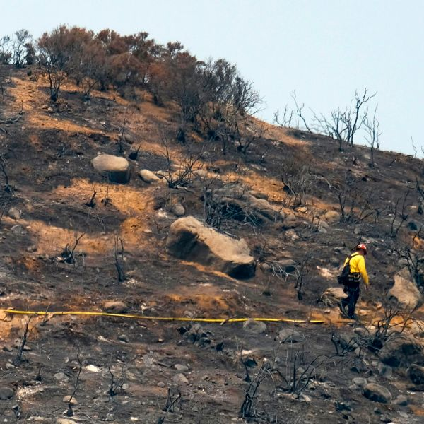 In this file photo taken on Aug. 10, 2018, firefighters walk through an area burned by the Holy Fire in Lake Elsinore. (Credit: Ringo Chiu / AFP / Getty Images)