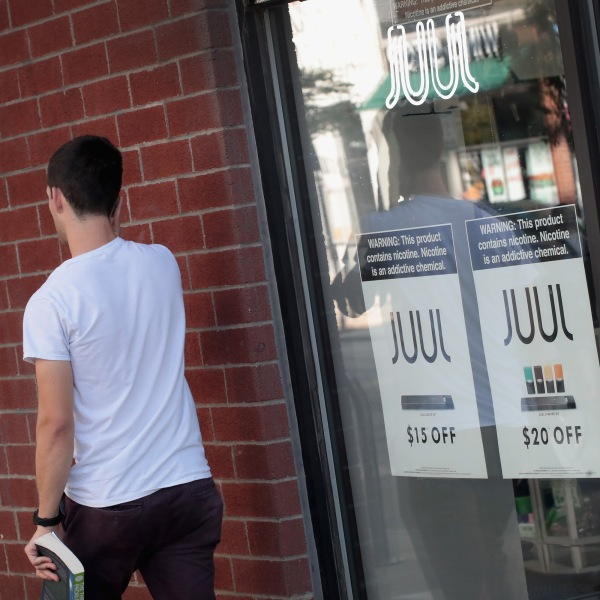 Signs in the window of the Smoke Depot in Chicago advertise electronic cigarettes and pods by Juul, the nation's largest maker of e-cigarette products, on Sept. 13, 2018. (Credit: Scott Olson/Getty Images)