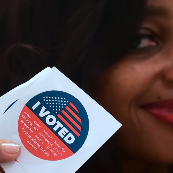 """Jetoi Johnson displays California's multi-language """"I Voted"""" sticker for those who vote at the Los Angeles County Registrar's Office in Norwalk on Nov. 5, 2018, a day ahead the midterm elections. (Credit: FREDERIC J. BROWN/AFP/Getty Images)"""