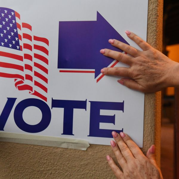 Poll workers attach a sign as they set up a voting station at Laguna Beach City Hall in Laguna Beach in Orange County California, before the polls open, November 6, 2018. (Credit: ROBYN BECK/AFP/Getty Images)
