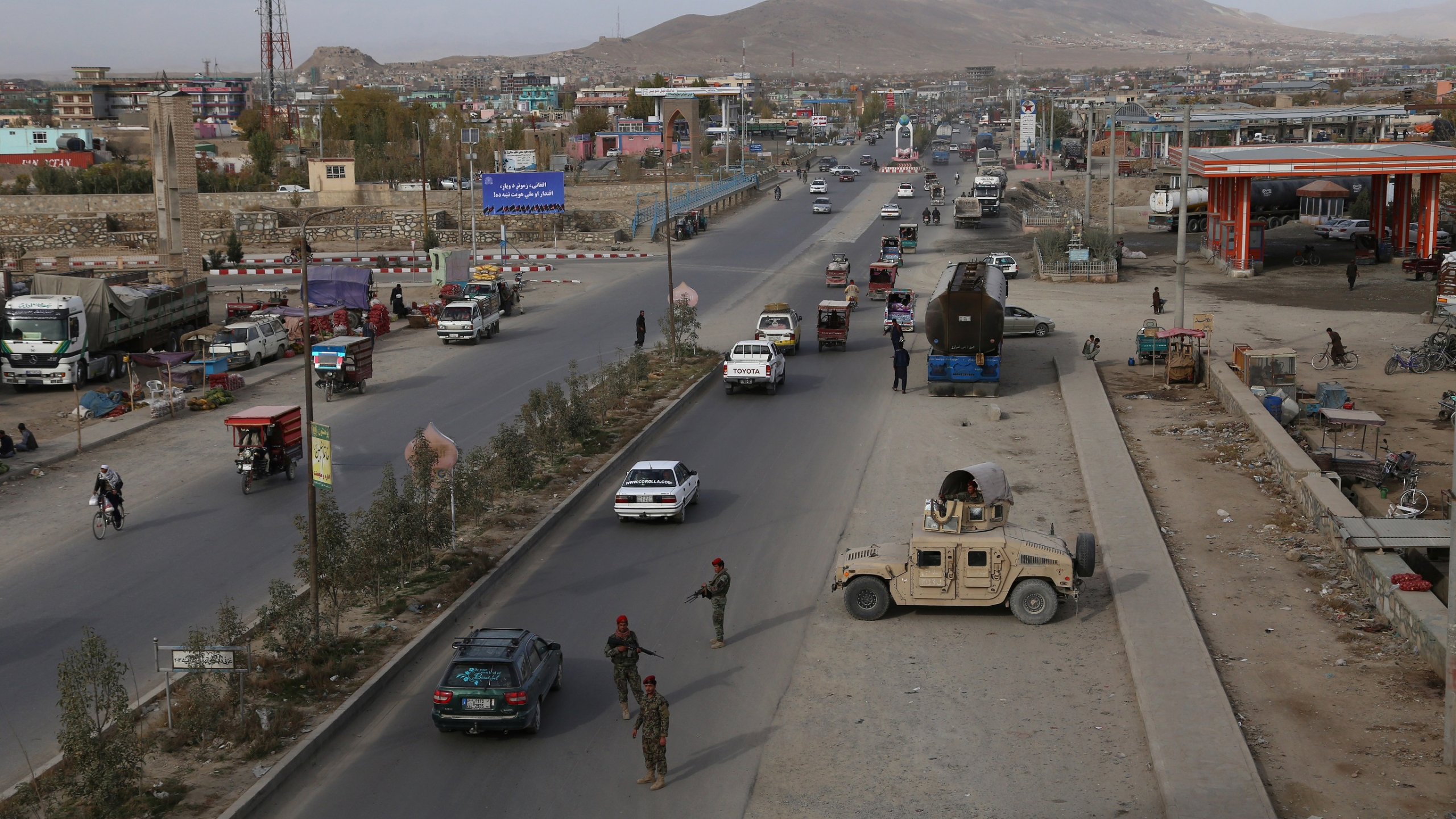 In this photo taken on October 29, 2018, Afghan security personnel search passengers in a checkpoint on Highway One in Ghazni. (Credit: ZAKERIA HASHIMI/AFP/Getty Images)