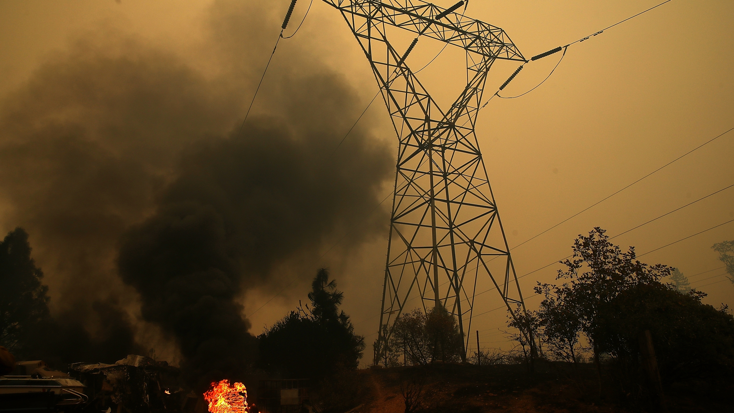 Smoke rises next to a power line tower after the Camp Fire moved through the area on November 9, 2018 in Big Bend, California. (Credit: Justin Sullivan/Getty Images)