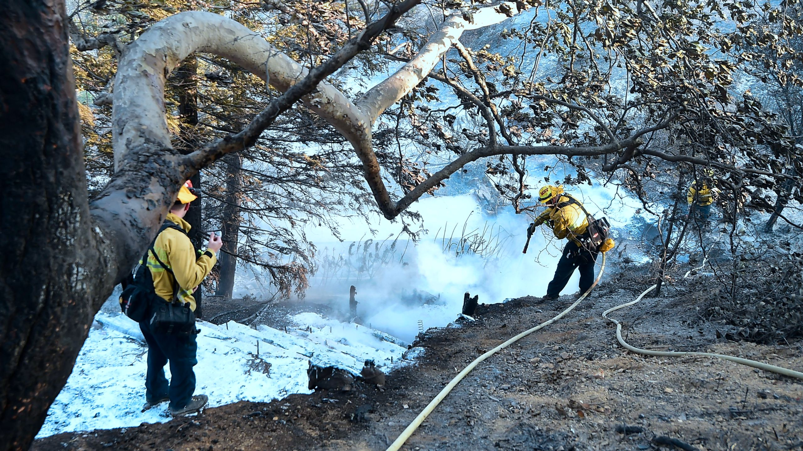 Firefighters spray foam on hot embers along a hillside near homes on Latigo Canyon Road in Malibu on Nov.10, 2018. (Credit: FREDERIC J. BROWN/AFP/Getty Images)