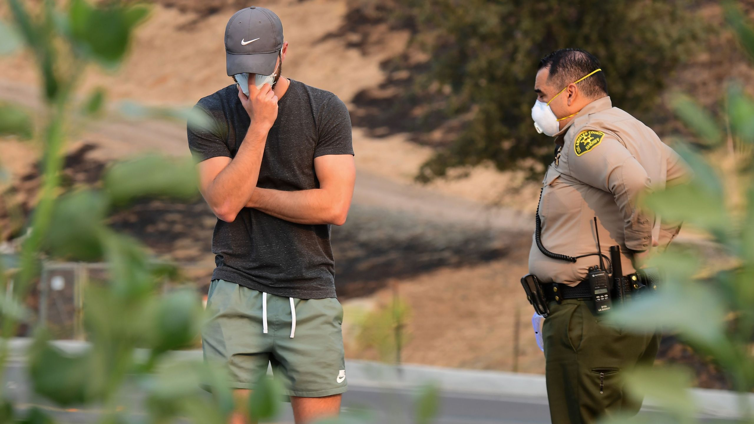 A local resident reacts after talking with a sheriff's deputy at a road block as the fight continues to control the Woolsey Fire, Nov. 10, 2018, in Calabasas. (Credit: ROBYN BECK/AFP/Getty Images)