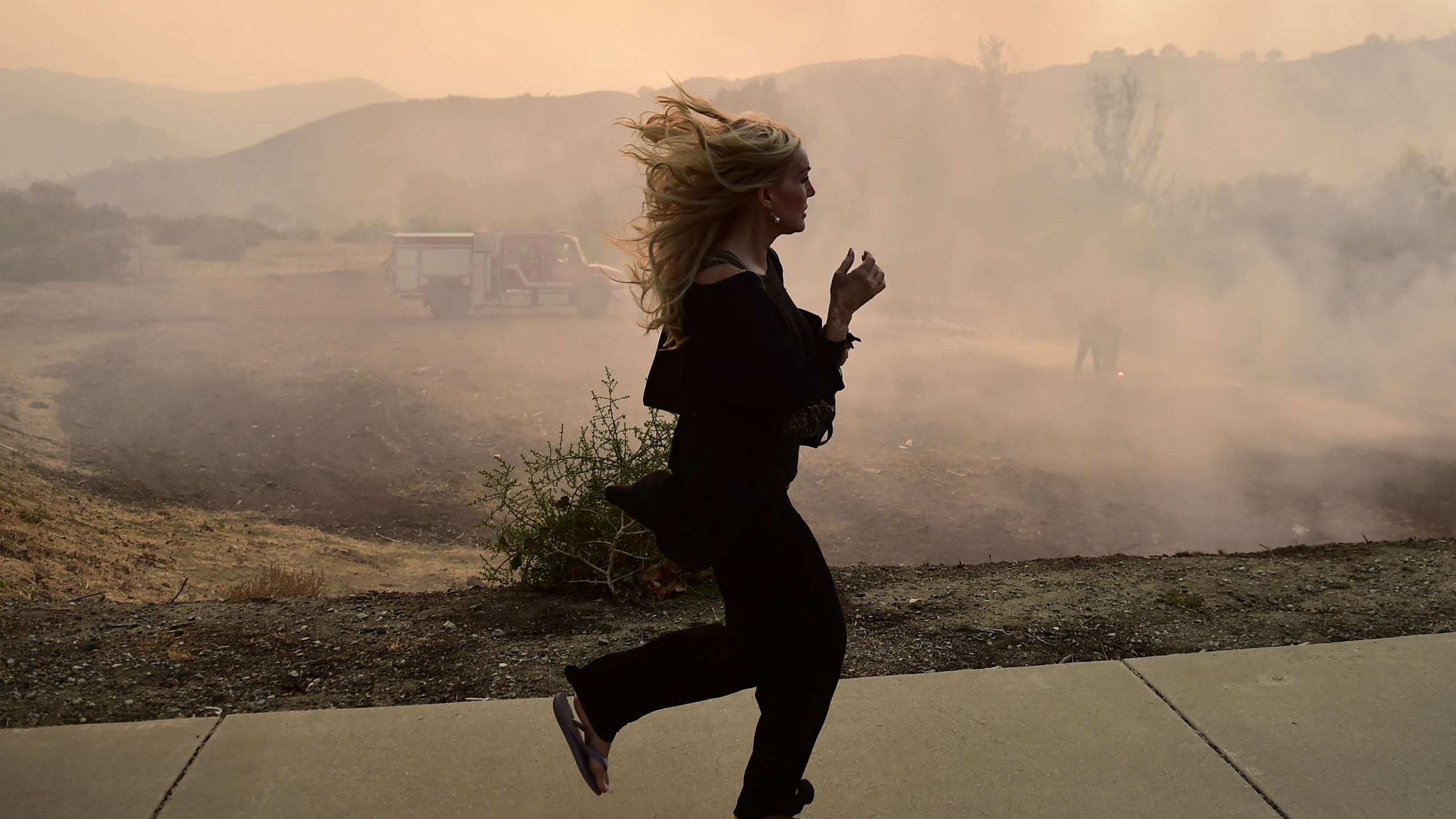 A woman runs as firefighters work to control a flare up due to flying embers from the Woolsey Fire, Nov. 10, 2018, in Calabasas on Nov. 10, 2018. (Credit: ROBYN BECK/AFP/Getty Images)