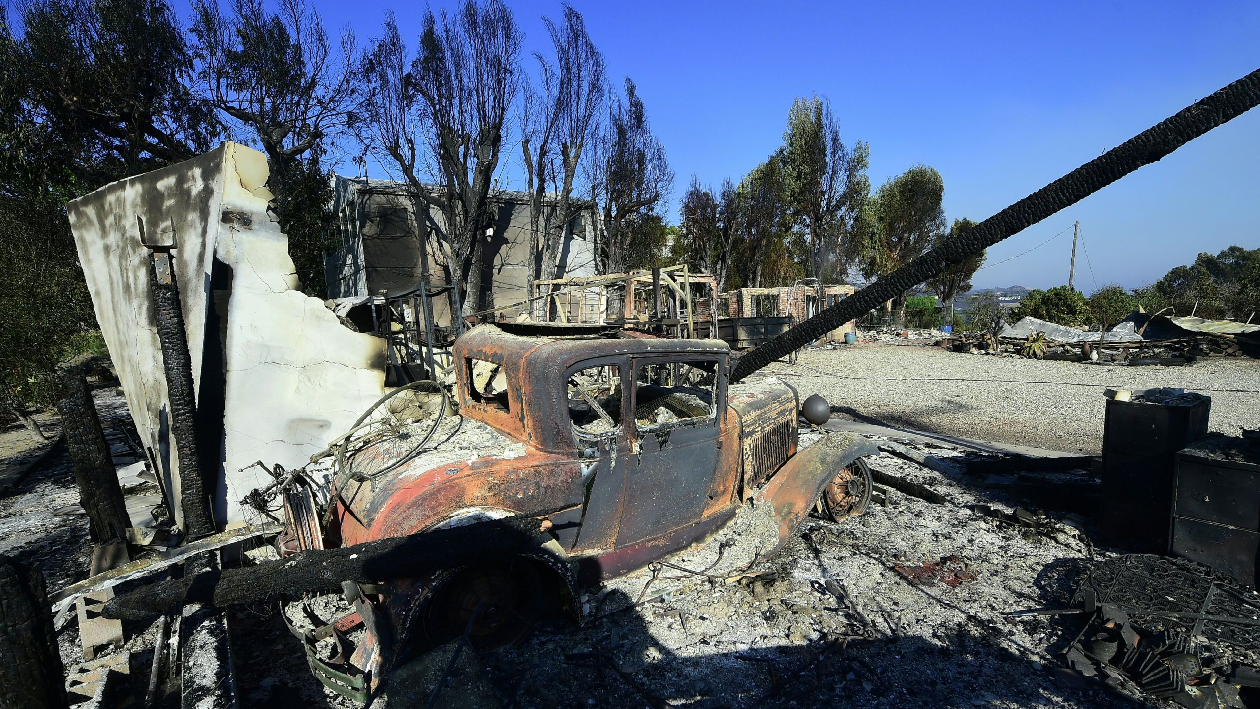 The remains of a fire-damaged home are seen off Kanan Dume Road, a canyon road which cuts across the mountains to Malibu, on November 11, 2018, as the battle to control the Woolsey Fire continues. (Credit: FREDERIC J. BROWN/AFP/Getty Images)