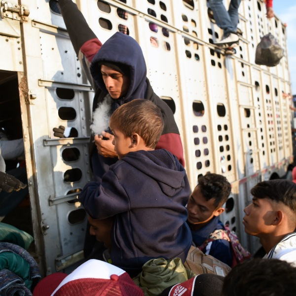 A child taking part in a caravan of migrants from Central American countries, mostly Hondurans, moving towards the United States in hopes of a better life, gets onto the trailer of a truck on the Irapuato-Guadalajara highway in the Mexican state of Guanajuato as they head to Guadalajara on their trek north, on Nov. 12, 2018. (Credit: ALFREDO ESTRELLA/AFP/Getty Images)