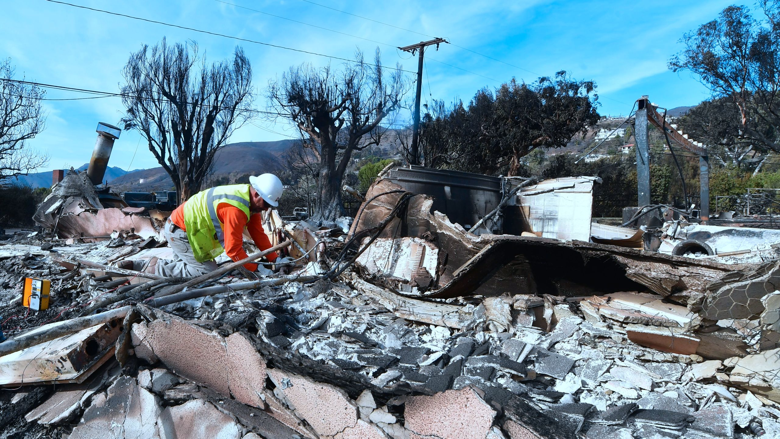 A worker checks gas lines amid the rubble of a home burnt down in the Woolsey Fire on Filaree Heights Road in Malibu on Nov. 13, 2018. (Credit: Frederic J. Brown/AFP/Getty Images)