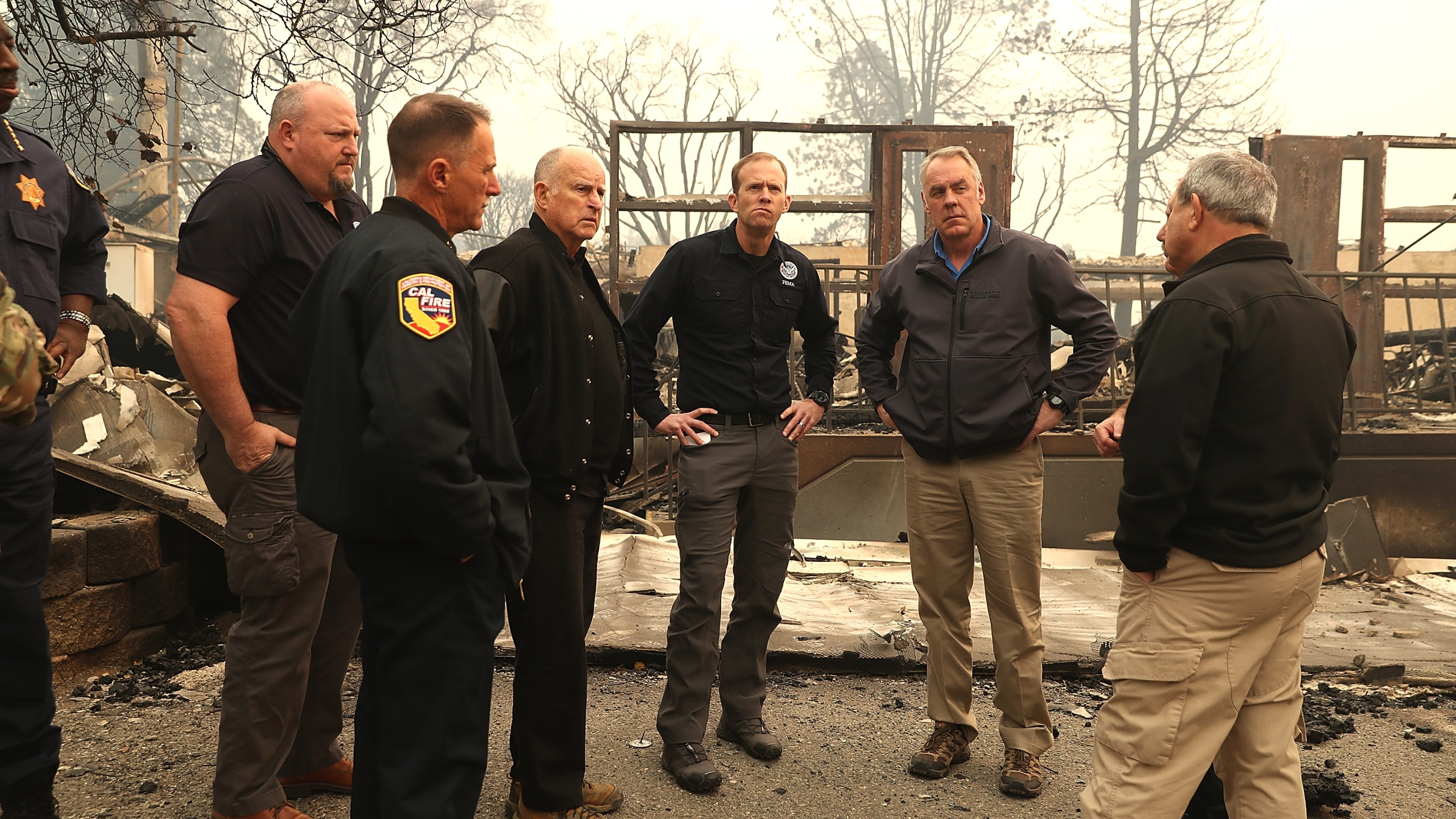 Gov. Jerry Brown and FEMA Adminstrator Brock Long and Secretary of the Interior Ryan Zinke tour a school burned by the Camp Fire on November 14, 2018 in Paradise. (Credit: Justin Sullivan/Getty Images)