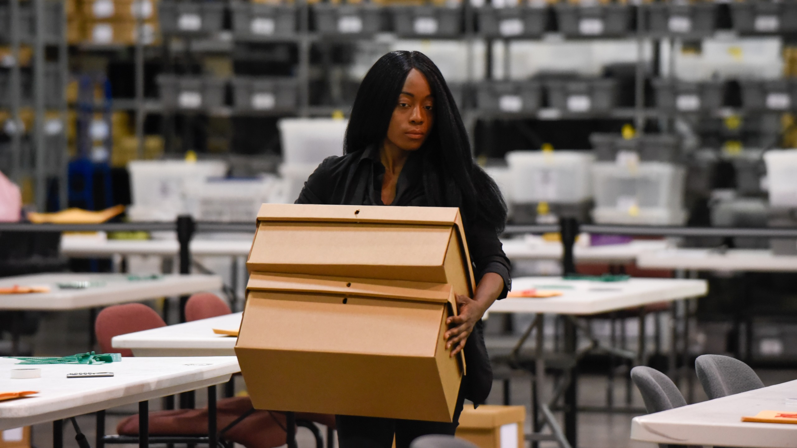 A woman sets up tables for hand counting ballots on November 15, 2018, as Palm Beach County did not meet the midterm recount deadline in West Palm Beach, Florida. (Credit: MICHELE EVE SANDBERG/AFP/Getty Images)
