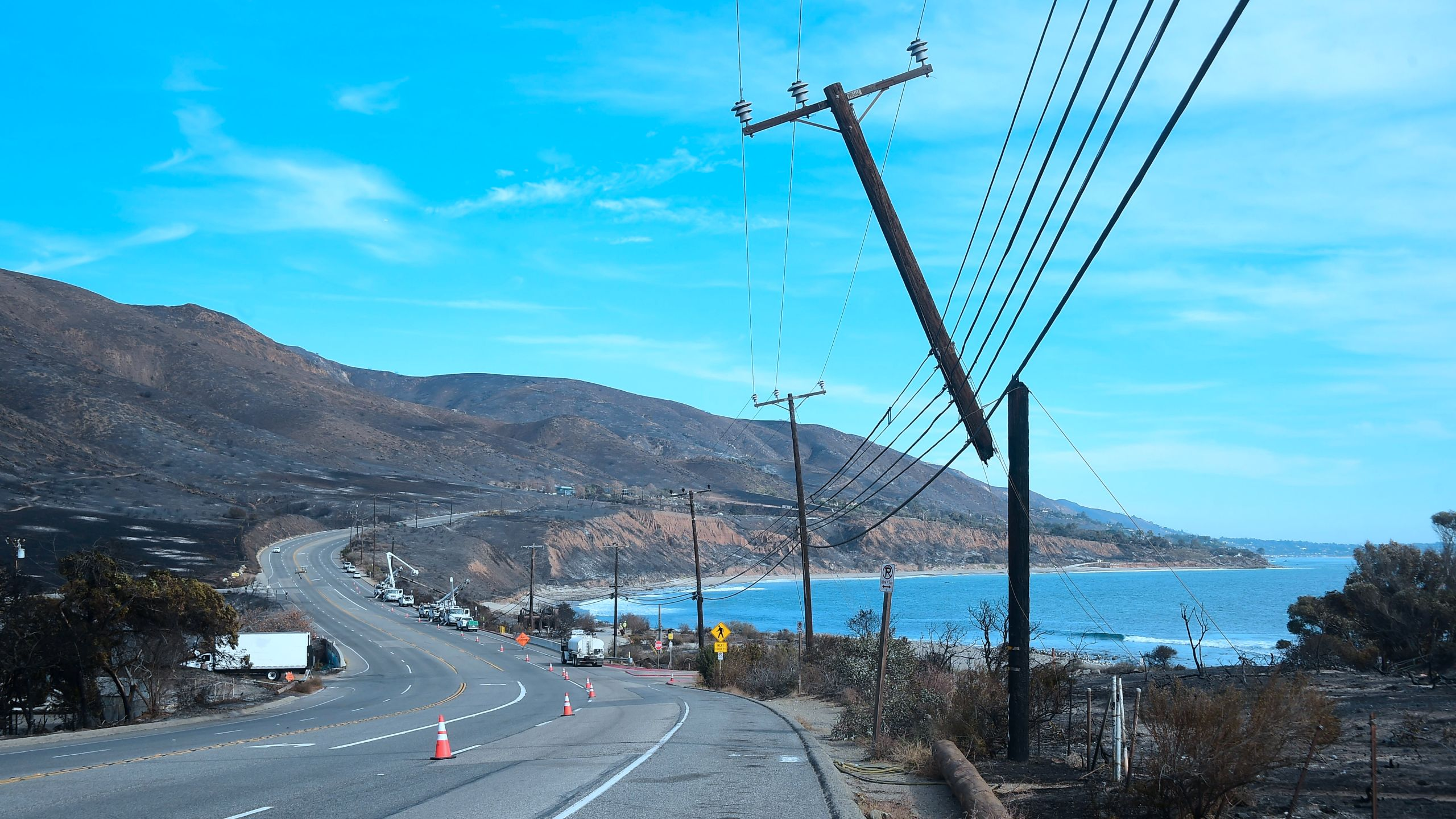 Power lines are repaired along the Pacific Coast Highway amid the blackened and charred hills from the Woolsey Fire in Malibu on Nov. 15, 2018. (Credit: FREDERIC J. BROWN/AFP/Getty Images)