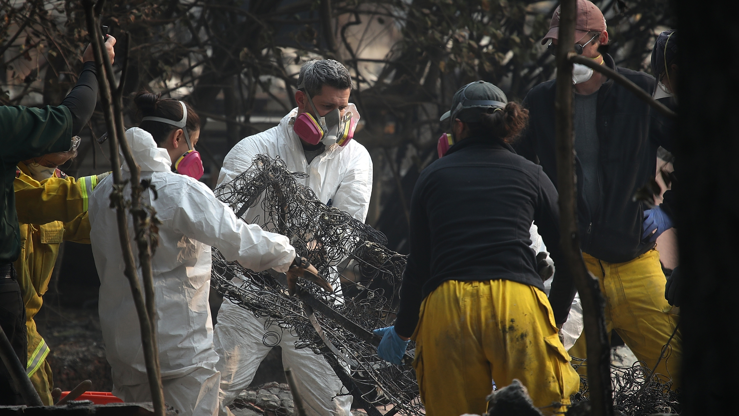 Rescue workers shake a burned mattress as they search for bone fragments while collecting human remains from a home destroyed by the Camp Fire on Nov. 16, 2018 in Paradise, California. (Credit: Justin Sullivan/Getty Images)