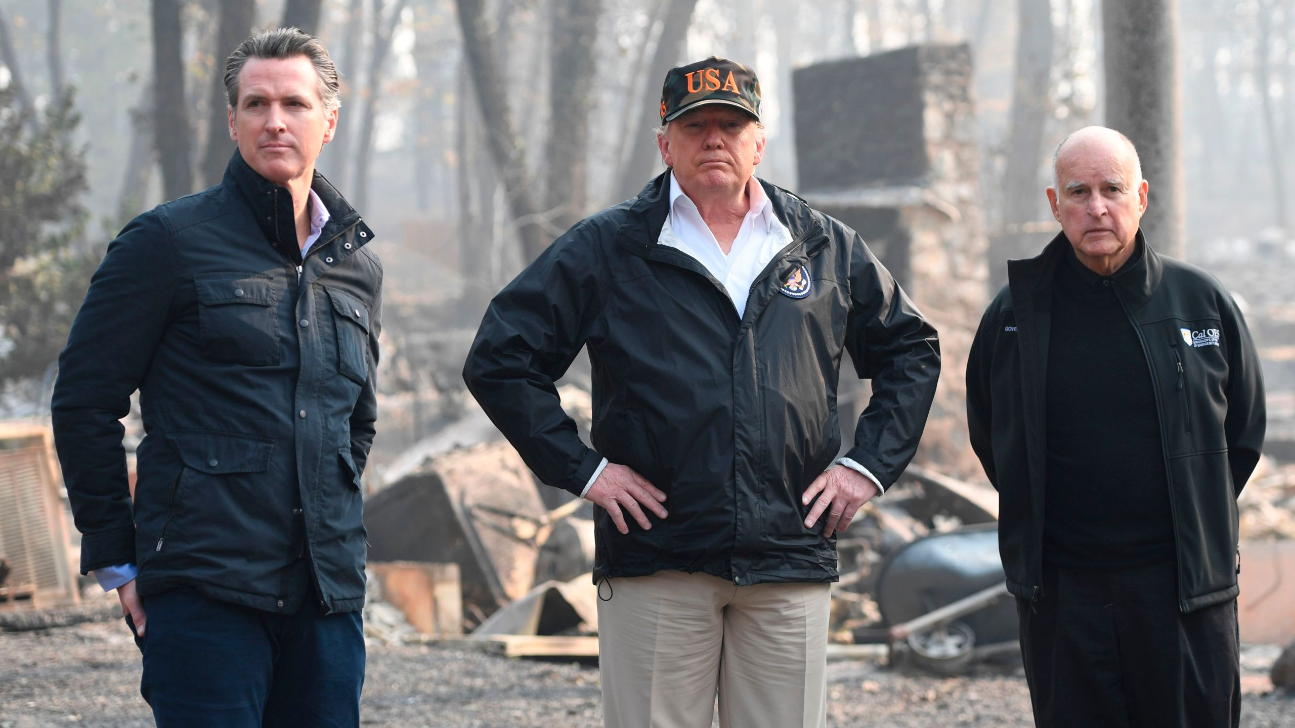 Donald Trump stands alongside Gov. Jerry Brown and Gov.-elect Gavin Newsom as they view damage from the Camp Fire in Paradise, California on Nov. 17, 2018. (Credit: SAUL LOEB/AFP/Getty Images)