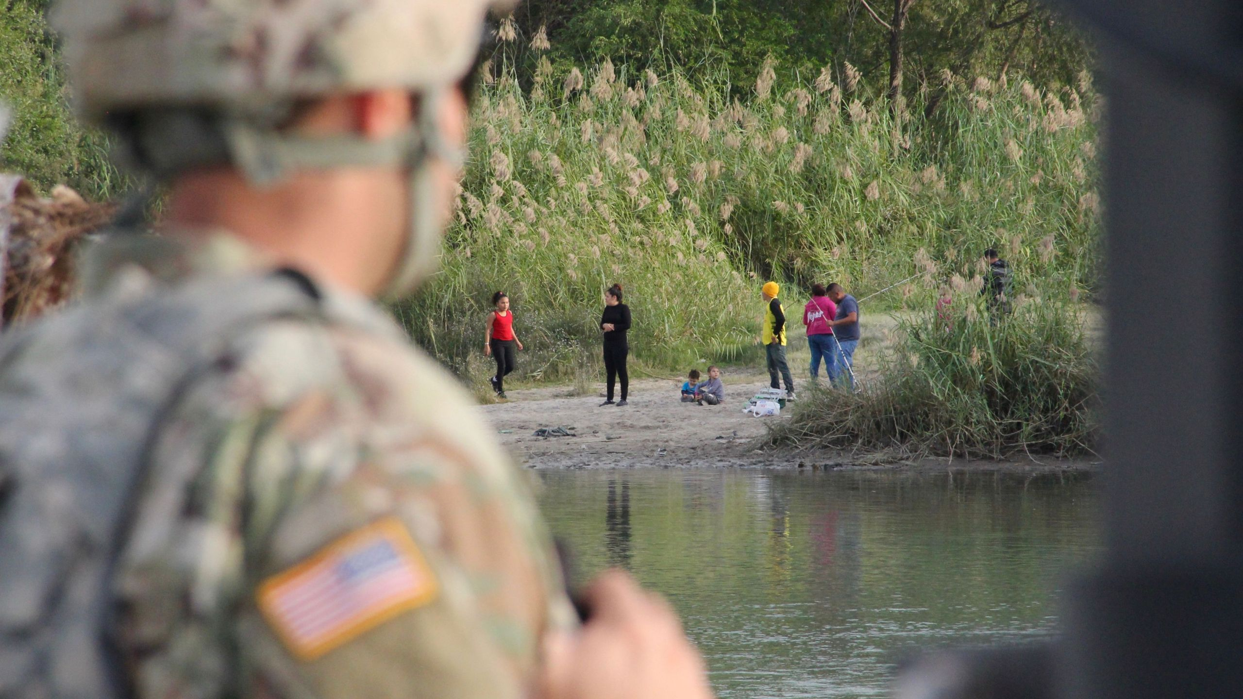 A soldier from the Kentucky-based 19th Engineer Battalion looks across the Rio Grande River from Laredo, Texas, into Nuevo Laredo, Mexico, where a group of people hang out on the river bank on Nov. 17, 2018. (Credit: Thomas Watkins / AFP / Getty Images)