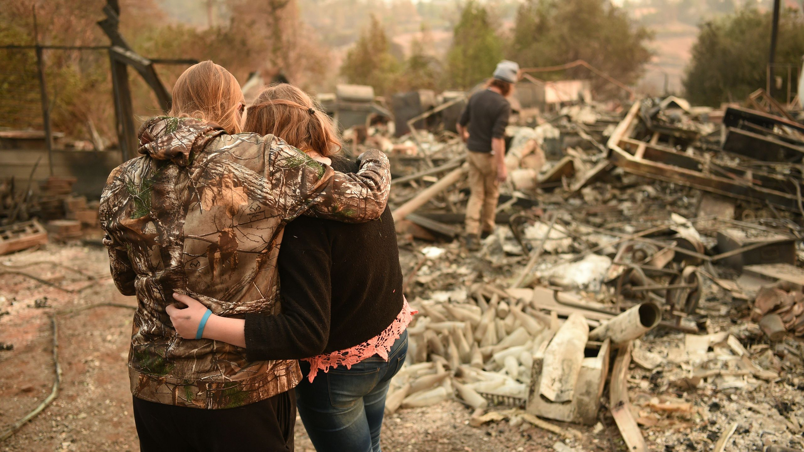 Kimberly Spainhower hugs her daughter Chloe, 13, while her husband, Ryan Spainhower, searches through the ashes of their burned home in Paradise on Nov. 18, 2018. (Credit: Josh Edelson / AFP / Getty Images)