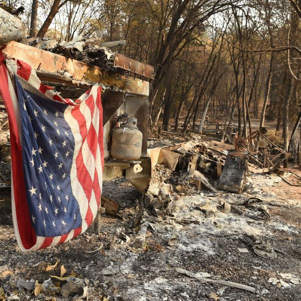 An American flag hangs at a burned out mobile home park in Paradise, California on Nov. 18, 2018. (Credit: Josh Edelson/AFP/Getty Images)