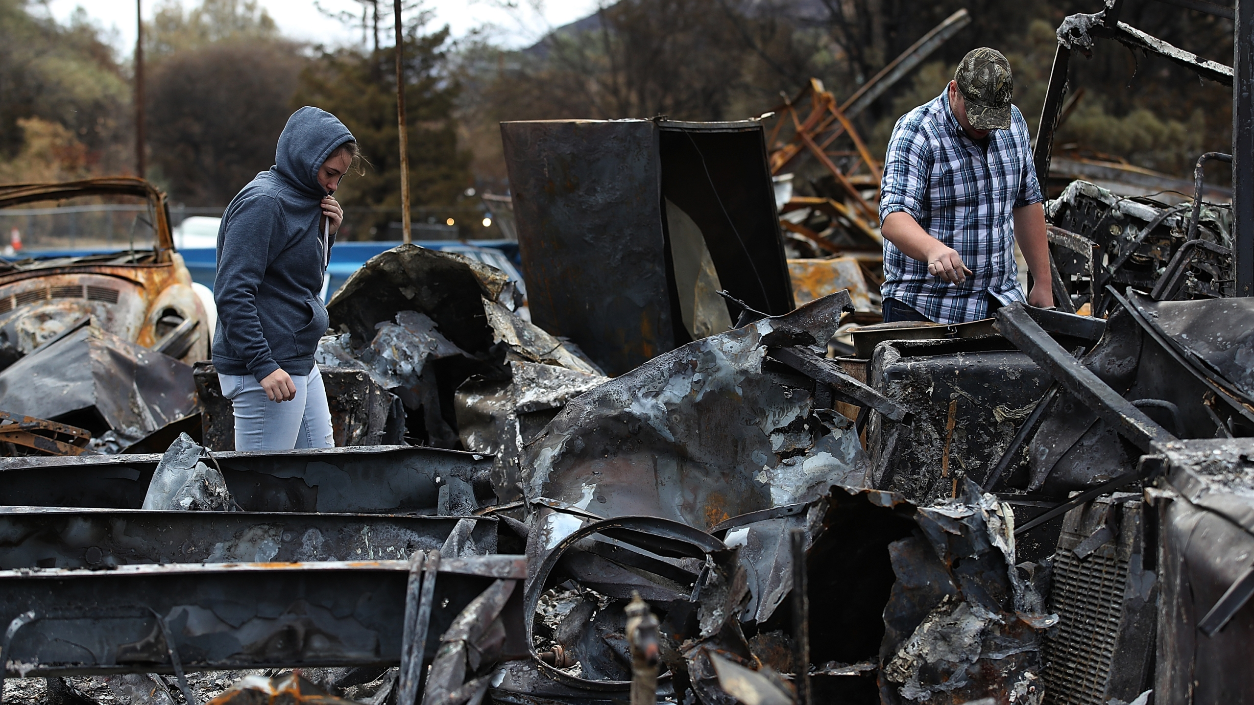 Noah Fisher, right, and Dusty Cope look through the remains of their home that was destroyed by the Camp Fire, Nov. 22, 2018, in Paradise. (Credit: Justin Sullivan / Getty Images)