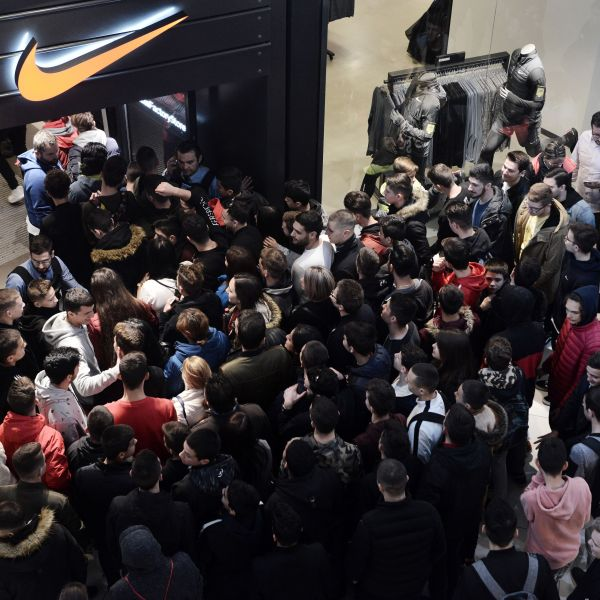 Customers wait at the entrance of a Nike sportswear store in Thessaloniki on Nov. 23, 2018,(Credit: SAKIS MITROLIDIS/AFP/Getty Images)