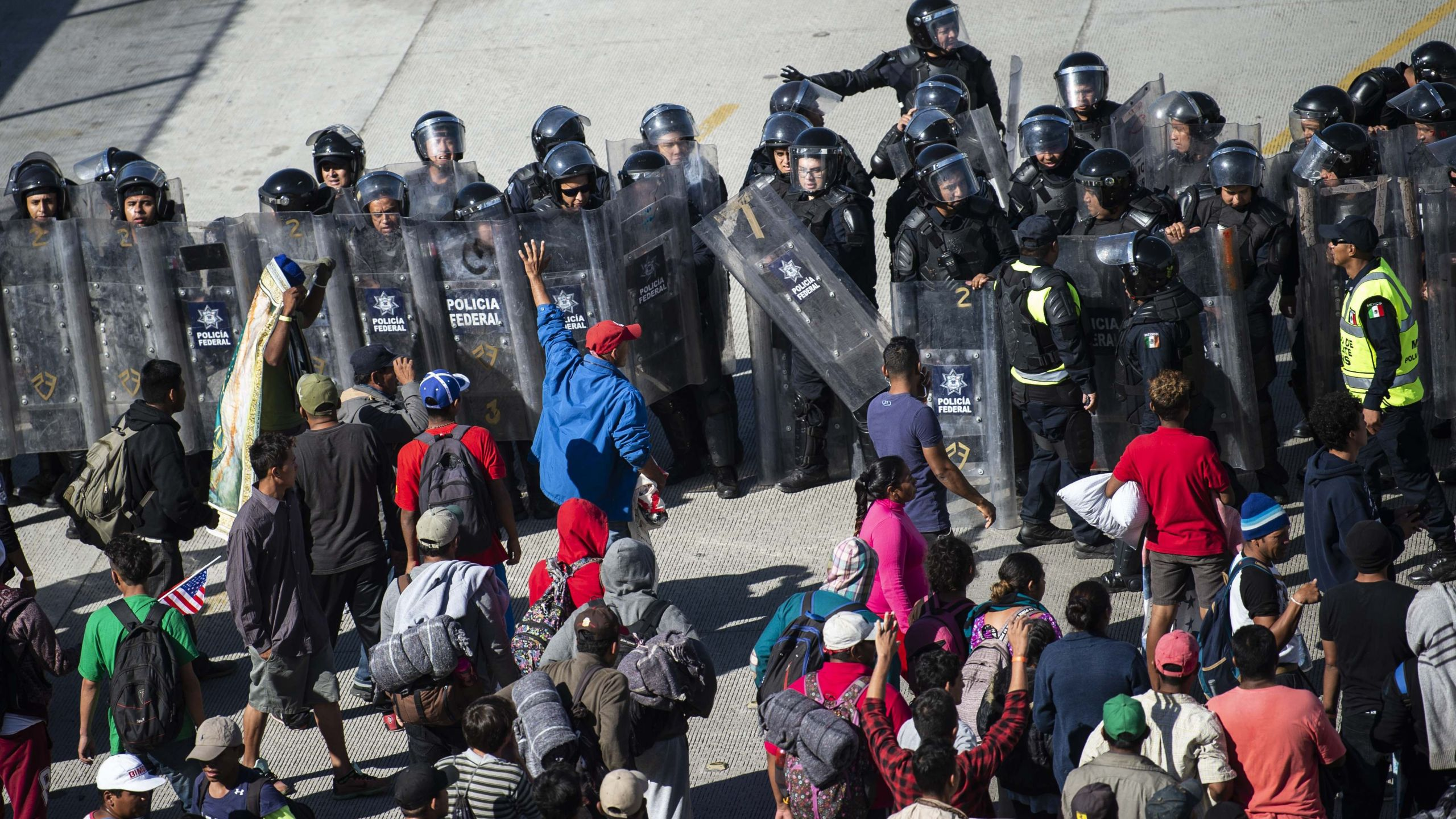 Central American migrants -mostly Hondurans- are blocked by Mexican police forces as they reach the El Chaparral border crossing, in Tijuana, Baja California State, Mexico, on November 25, 2018.
