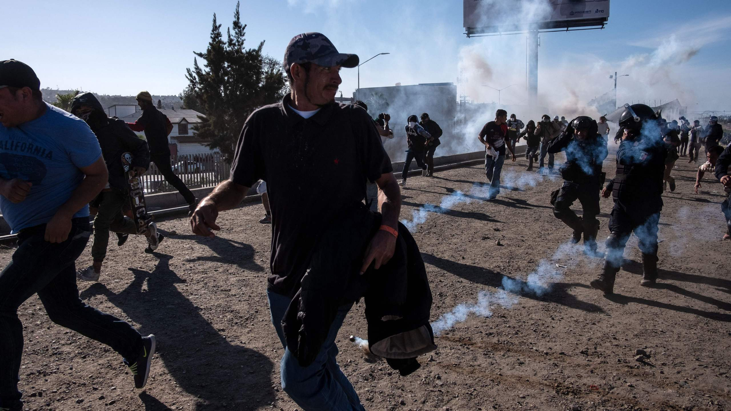 Central American migrants -mostly Hondurans- run along the Tijuana River near the El Chaparral border crossing in Tijuana, Baja California State, Mexico, near US-Mexico border, after the US border patrol threw tear gas from the distance to disperse them after an alleged verbal dispute, on November 25, 2018. (Credit: GUILLERMO ARIAS/AFP/Getty Images)