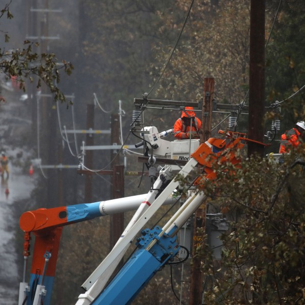 Pacific Gas and Electric crews repair power lines in Paradise that were destroyed by the Camp Fire, Nov. 21, 2018. (Credit: Justin Sullivan / Getty Images)