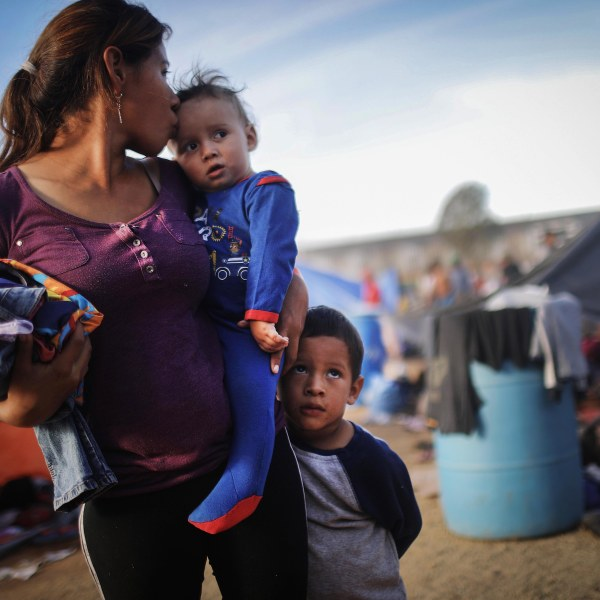 A Honduran mother stands with her sons at a temporary shelter for migrants on Nov. 21, 2018 in Tijuana, Mexico. (Credit: Mario Tama/Getty Images)
