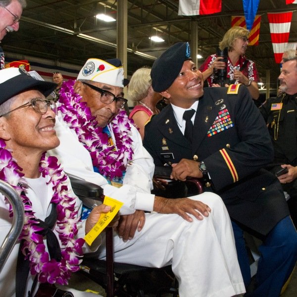 Pearl Harbor survivor Ray Chavez, center, sits with his daughter Kathleen Chavez, left, and Chief Warrant Officer 4 Dorian Bozza, right, during a ceremony commemorating the 75th anniversary of the attack on Pearl Harbor at Kilo Pier on Dec. 7, 2016. (Credit: Craig T. Kojima / Getty Images)