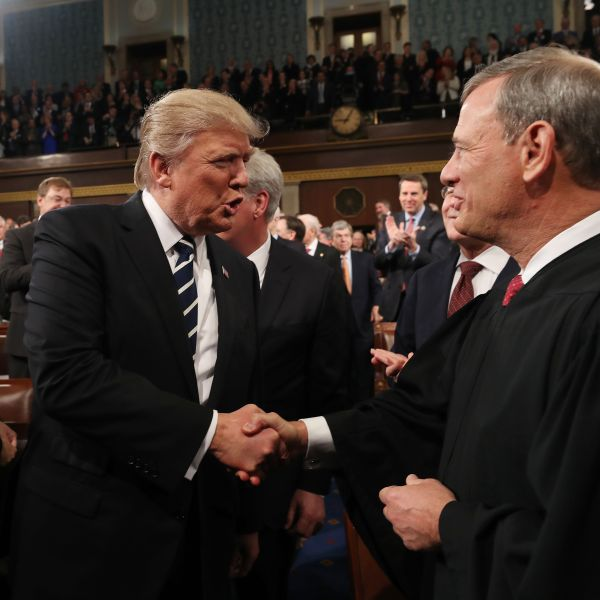 Donald Trump shakes hands with Chief Justice John Roberts as he arrives to deliver his first address to a joint session of Congress from the floor of the House of Representatives in Washington, D.C. on Feb., 28, 2017. (Credit: JIM LO SCALZO/AFP/Getty Images)