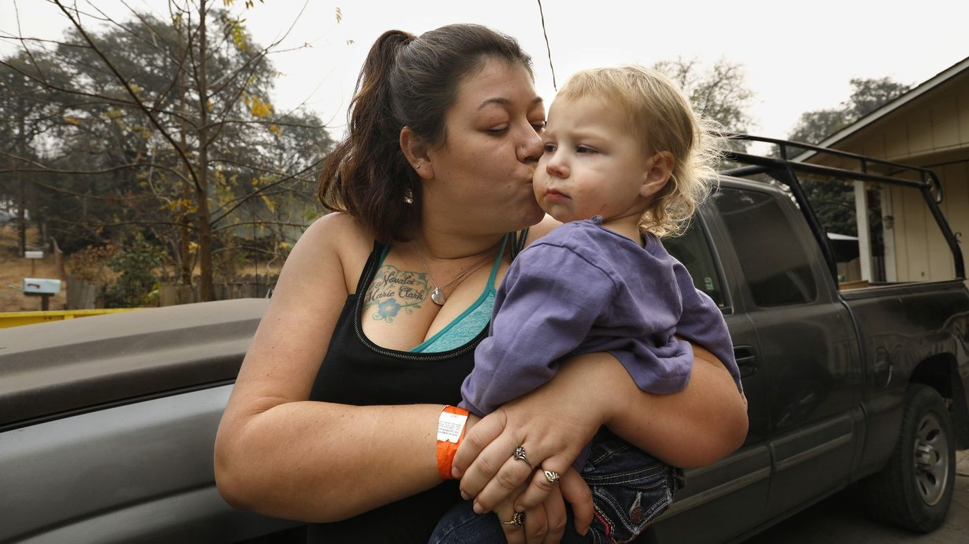 Megan Butler, holds her daughter Aurora, 2, after their home in the tiny community of Concow burned down in the Camp Fire in November 2018. (Credit: Carolyn Cole / Los Angeles Times)